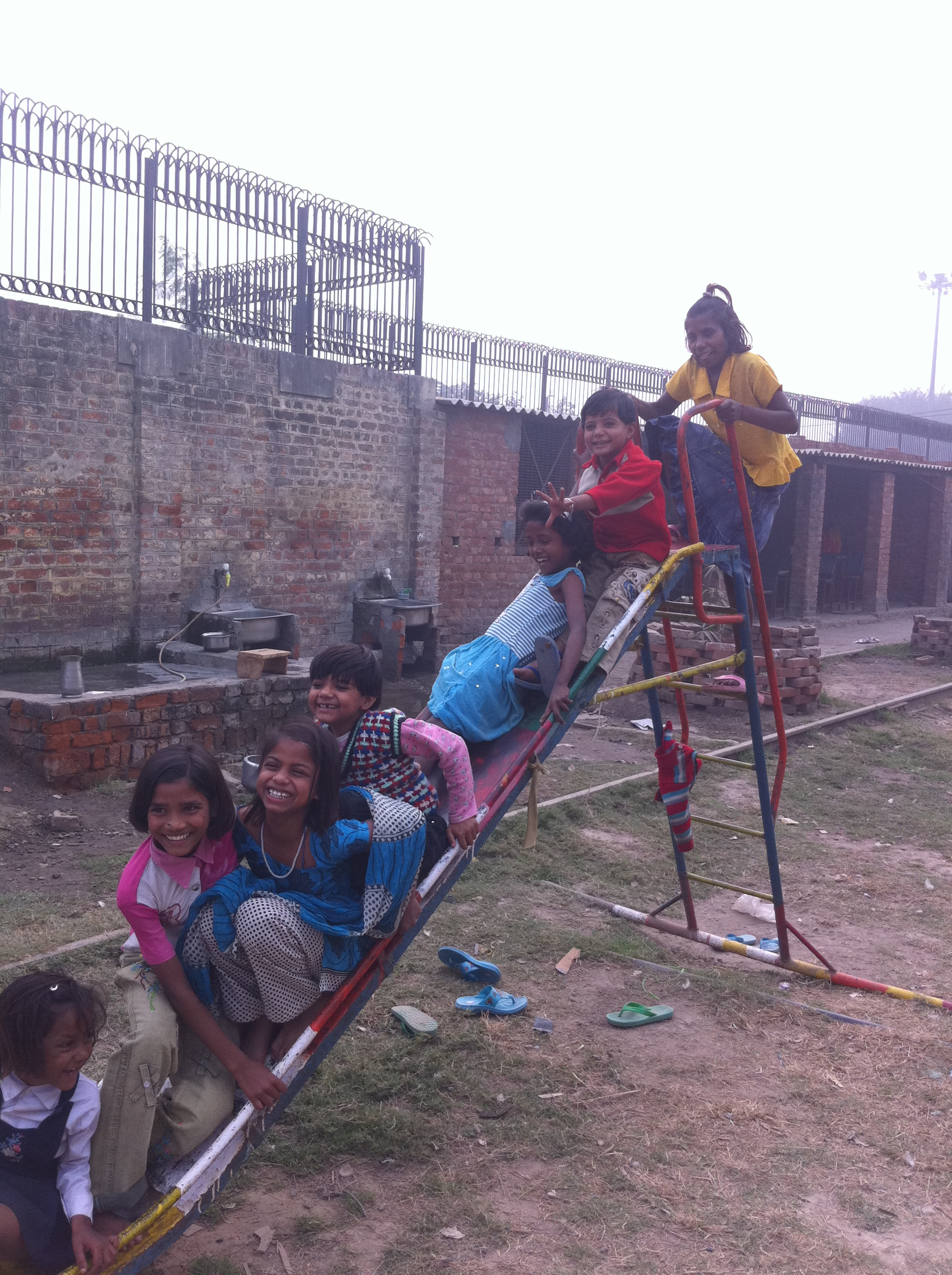 Photo of kids crowded onto a slide at our Delhi Home
